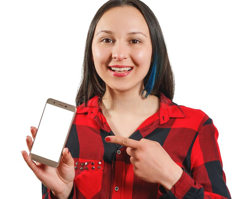 A young girl in a red and black shirt holds a smartphone with an empty white screen vertically in front of her, points at it with. Her finger and smiles at the stock photography