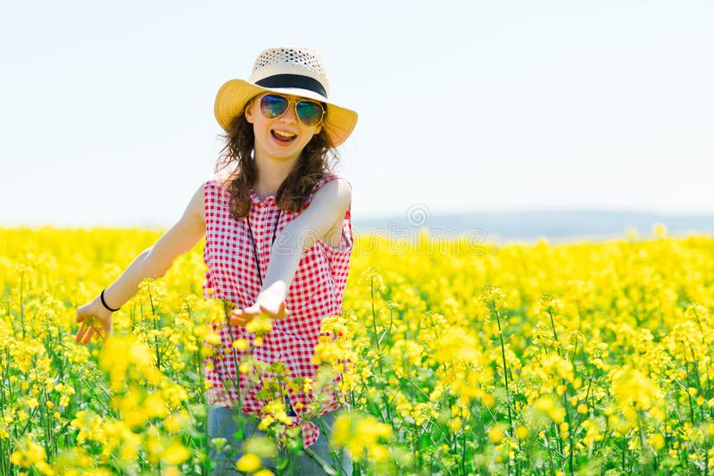 Young girl in red checkered dress and sunhat posing in oilseed rape field royalty free stock photography
