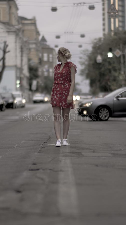 Young girl in red dress look at the distance standing at the urban road royalty free stock photography