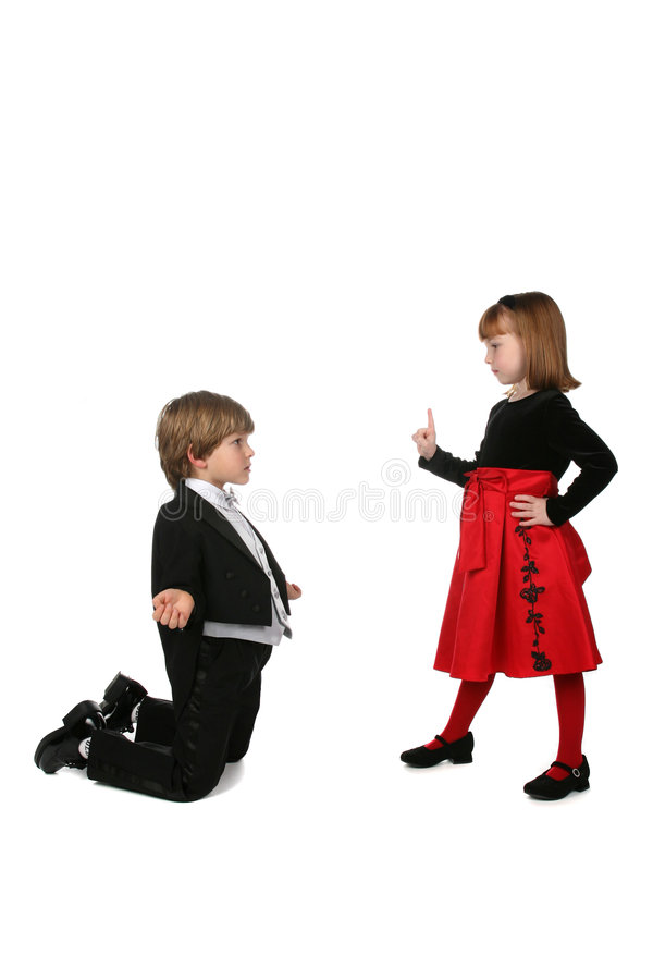 Young girl in red dress scolding boy in tuxedo stock photo