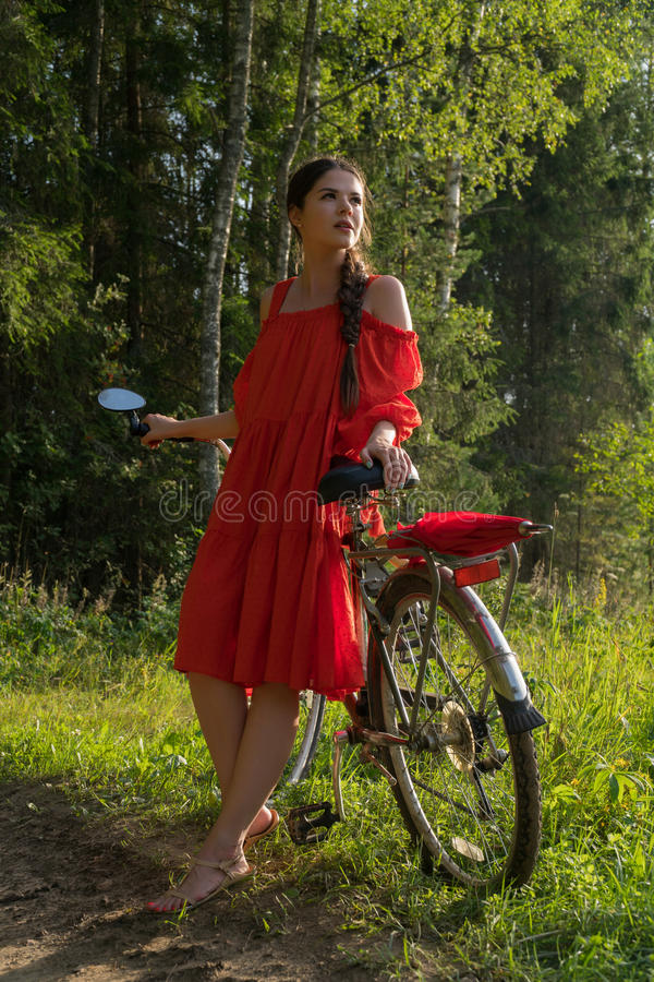 A young girl in a red dress is standing near a bicycle with a red umbrella. In the background there is a forest royalty free stock photography