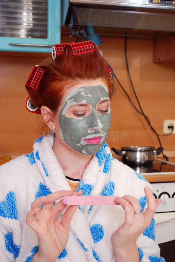 The young girl with red hair in hair curlers with a clay face pack in kitchen does manicure. Home stage stock photos