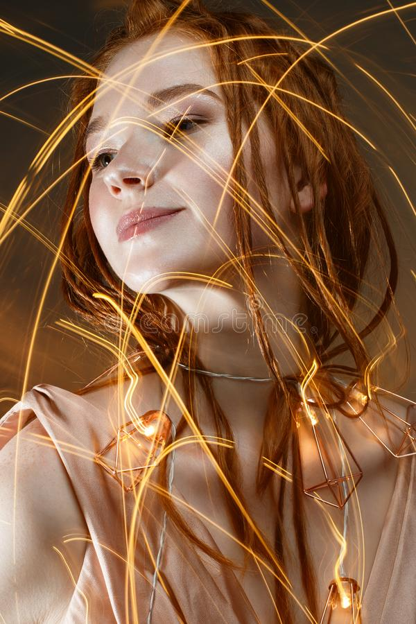 A young girl with red hair and with a luminous garland. Beautiful model with shining bulbs and lights. Gentle makeup. stock photos
