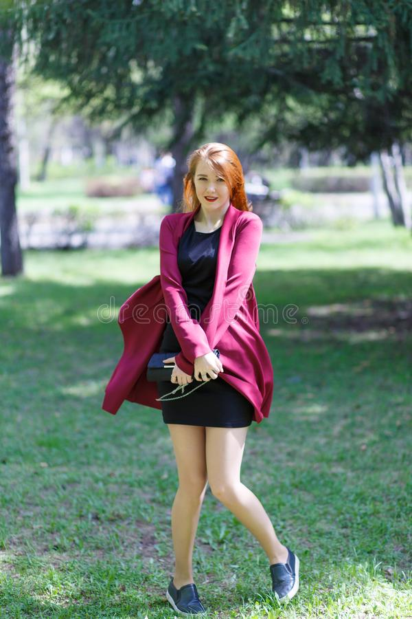 A young girl with red hair walks in the Park in a good mood. Happy girl. stock photos