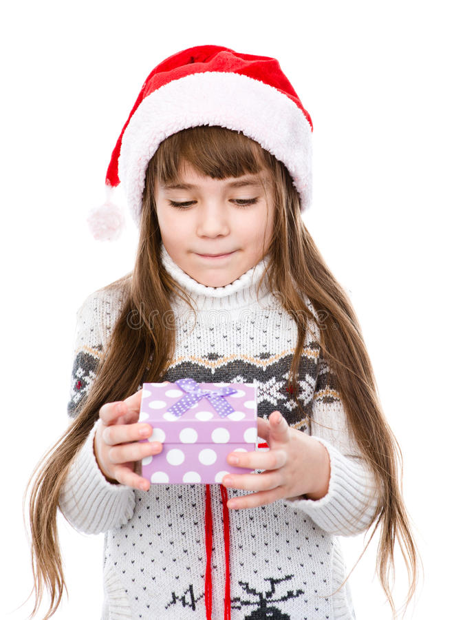 Young girl in red santa hat holding gift box. looking on gift. isolated on white stock images