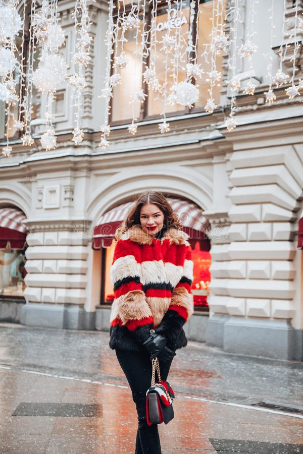 Young russian girl on the red Square through winter holiday in Moscow, stylish and beautiful posing near to Gum. Young girl on the red Square through winter royalty free stock photo