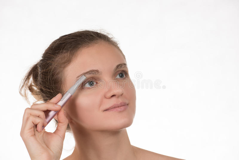 Young girl in a red towel caring for your eyebrows with trimmer royalty free stock images