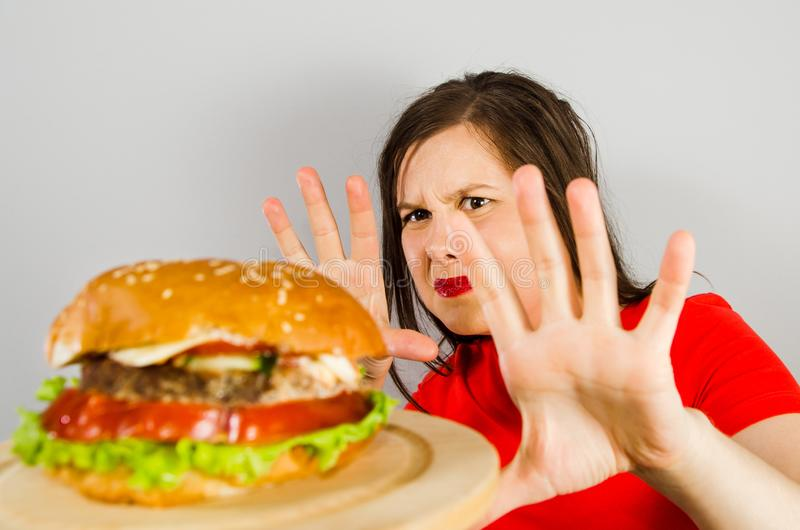 Young girl refuses fat unhealthy hamburger because she is losing weight and dieting on gray background stock image