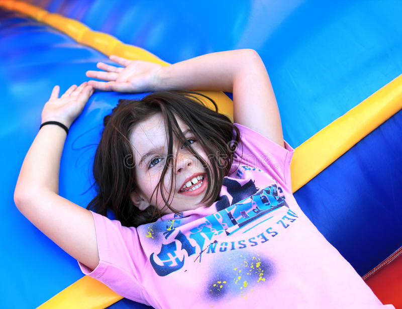 Young girl relaxing. A beautiful color portrait of a young girl relaxing after having fun royalty free stock image