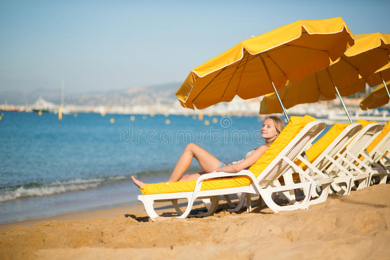 Young girl relaxing on a beach chair near the sea. Beautiful girl relaxing on a beach chair near the sea royalty free stock photo