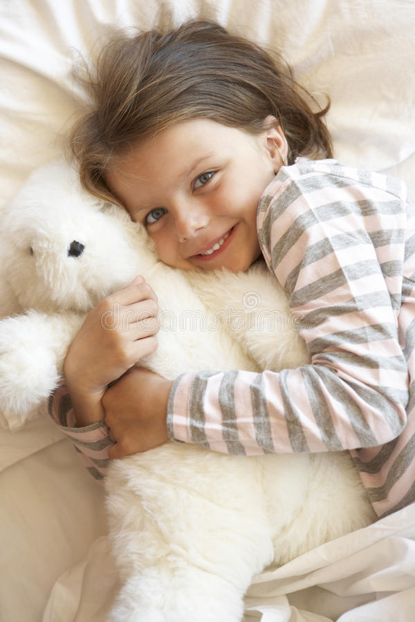 Young Girl Relaxing In Bed With Toy royalty free stock image