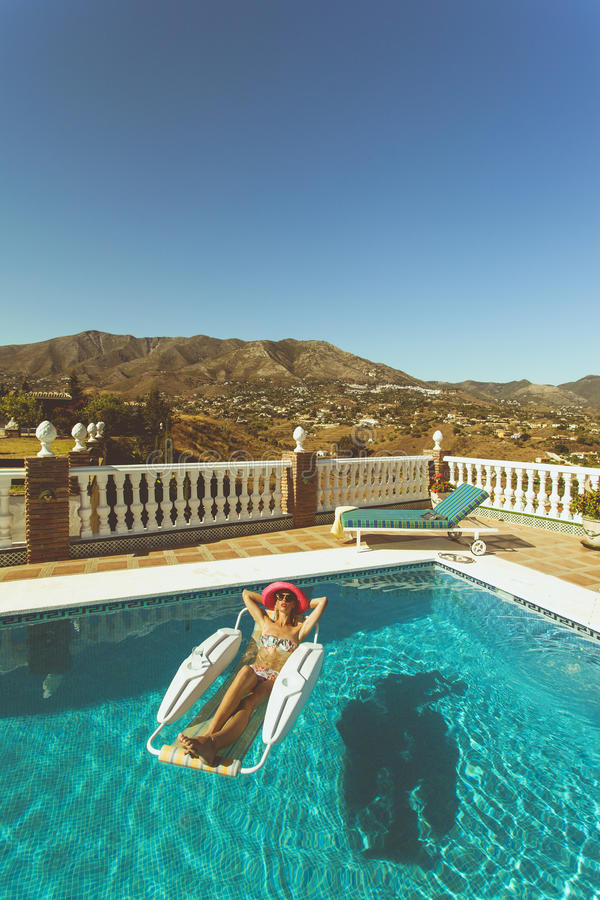 Young girl relaxing in pool in Spain stock images