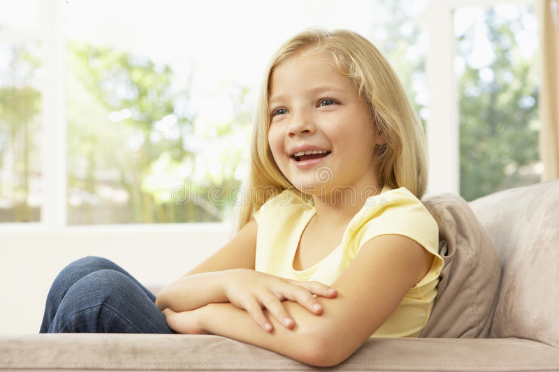 Young Girl Relaxing On Sofa At Home. Smiling royalty free stock photo