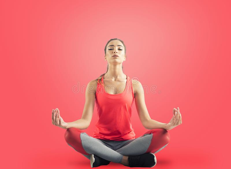 Young girl relaxing in yoga position on red background royalty free stock photography