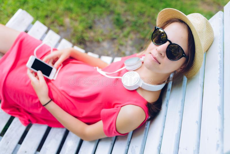 Young girl resting on a wooden chair in the garden. Young girl resting on a hanging wooden chair in the garden - with headphones around her neck and a smartphone stock images