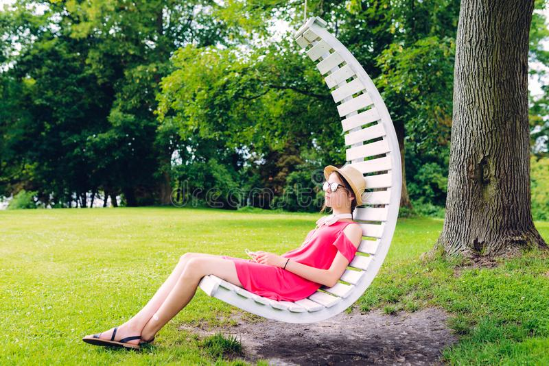 Girl resting on a hanging wooden chair in the garden. Young girl resting on a hanging wooden chair in the garden, relaxation, comfortable, happy, tree, outdoor stock images