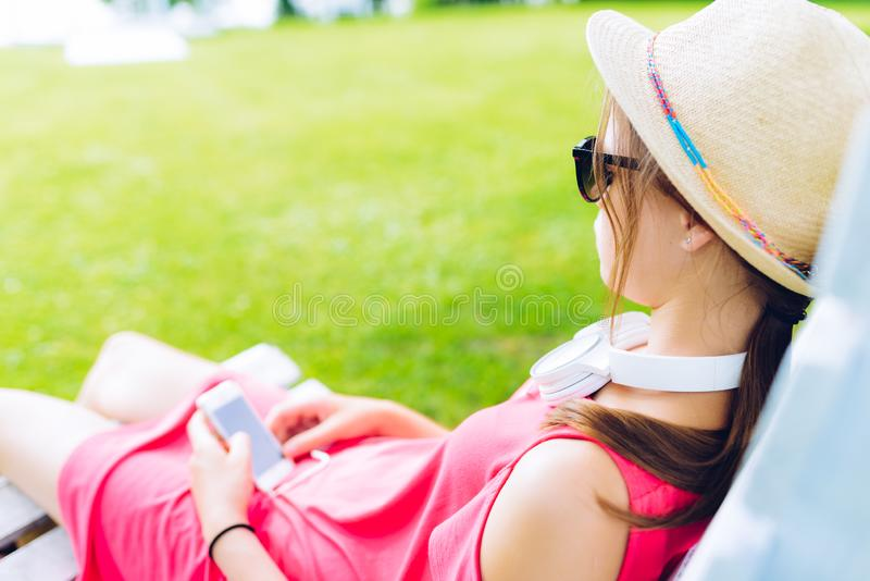 Young girl resting on a wooden chair in the garden. Young girl resting on a hanging wooden chair in the garden - with headphones around her neck and a smartphone stock photo