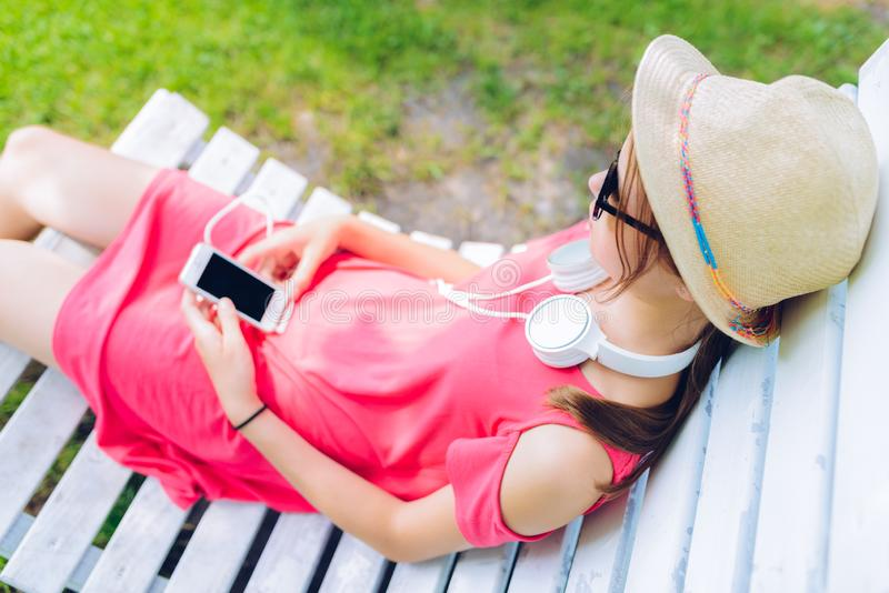 Young girl resting on a wooden chair in the garden. Young girl resting on a hanging wooden chair in the garden - with headphones around her neck and a smartphone stock image