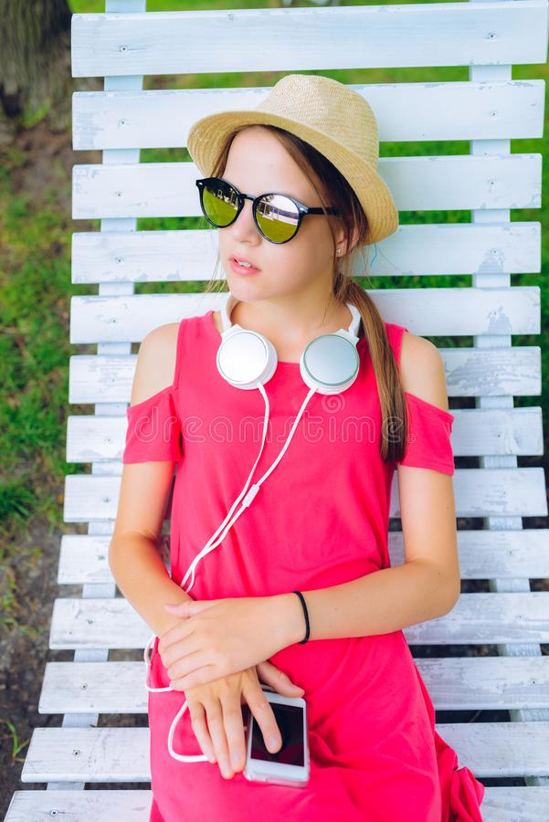 Young girl resting on a wooden chair in the garden. Young girl resting on a hanging wooden chair in the garden - with headphones around her neck and a smartphone royalty free stock photography
