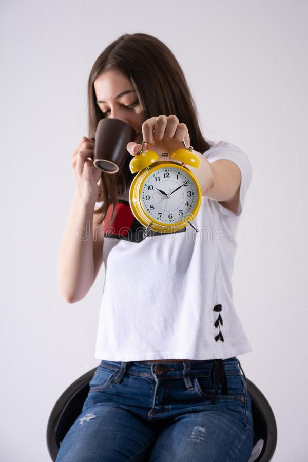 Young girl with retro clock in hand showing time and drinking coffee isolated on white background royalty free stock photos