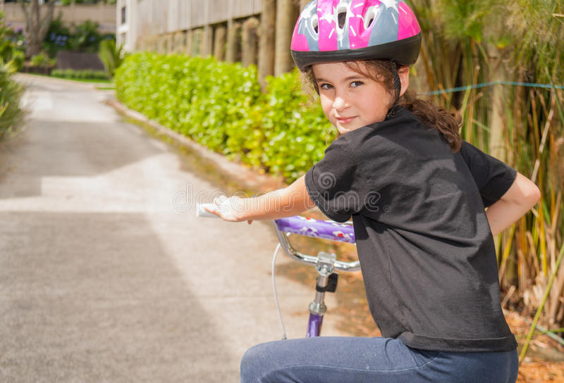 Young girl riding bicycle wearing helmet turns her head and look. S back with a smila royalty free stock image