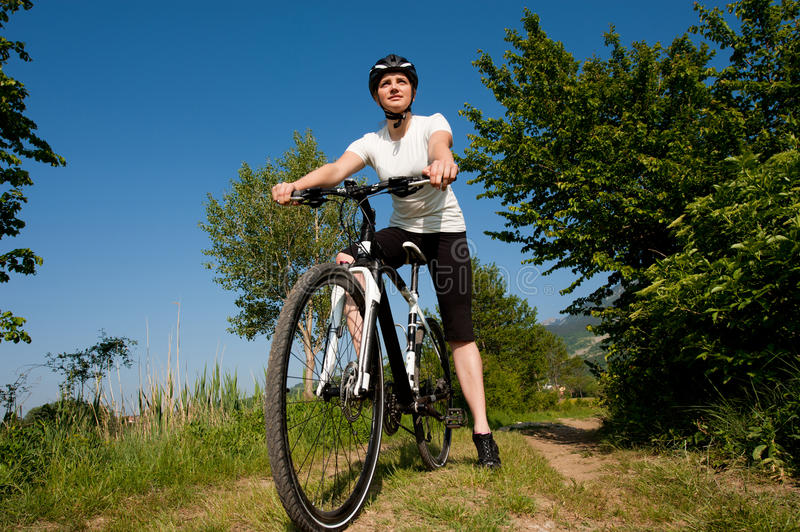 Young girl riding a bike offroad royalty free stock photography