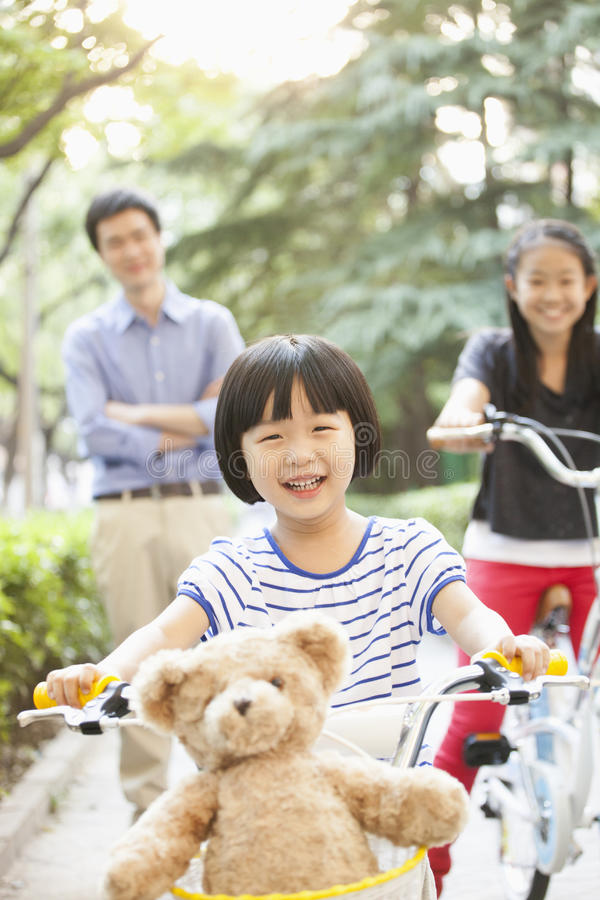 Young Girl Riding Her Bicycle with Her Family stock photo