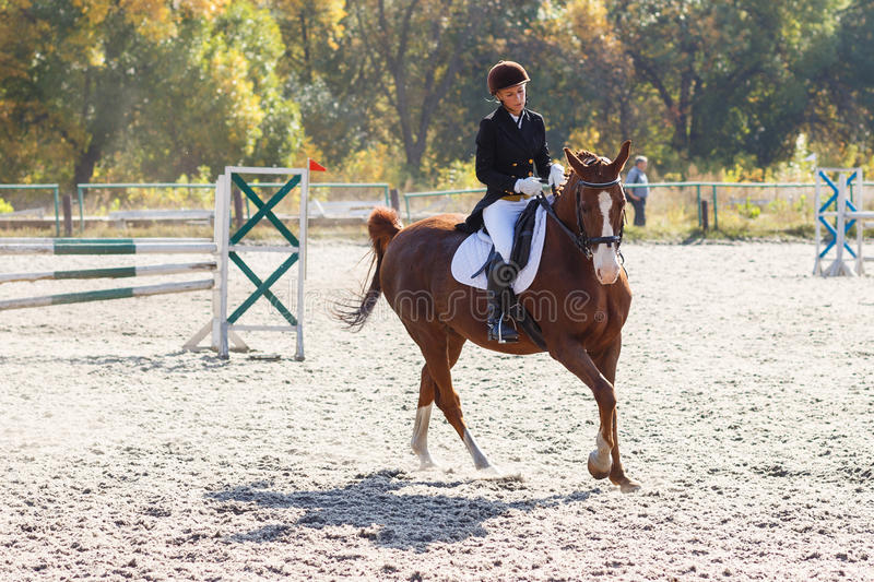 Young girl riding horse in equestrian competition stock photography