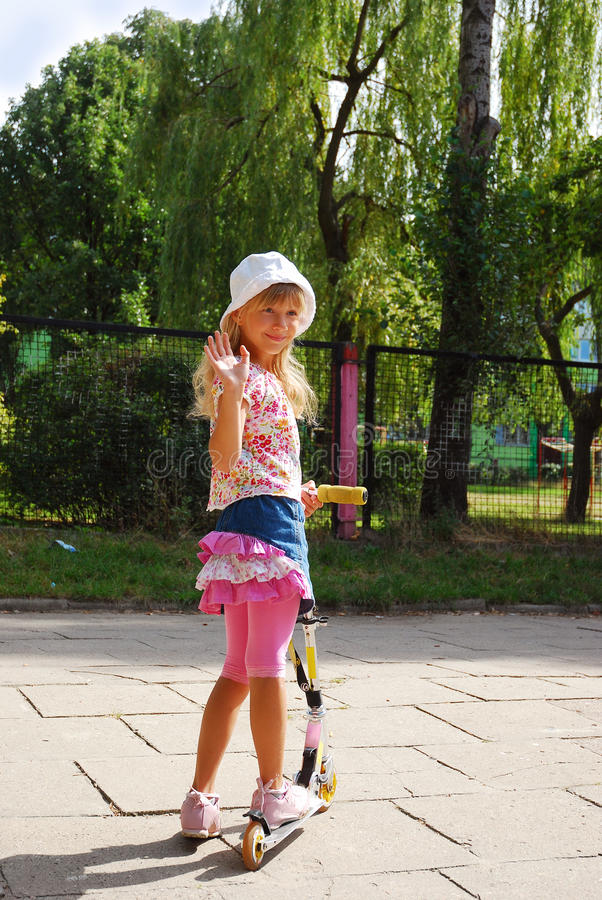 Download Young Girl Riding Scooter  Waving Hand To Friends Stock Image - Image: 15331849