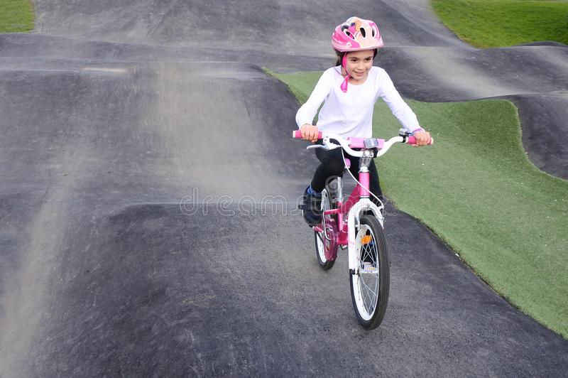 Young Girl Rids Bicycle on Obstacle Trek royalty free stock photography