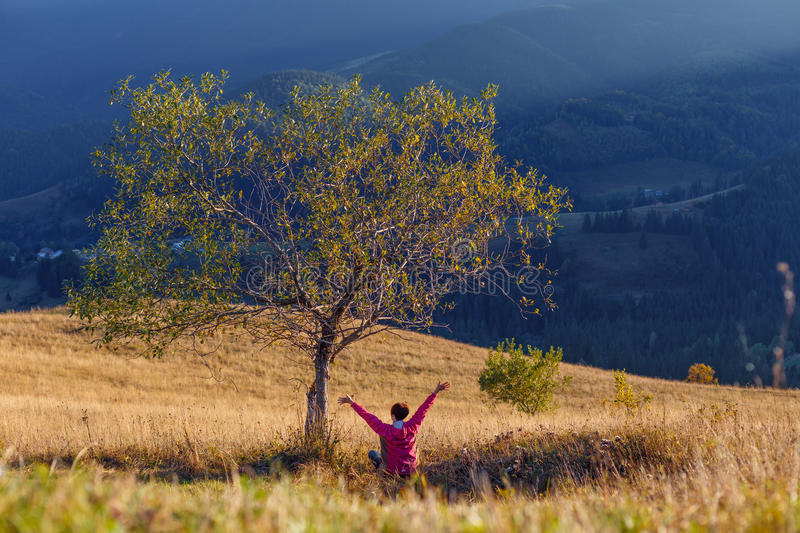Young girl rises up her hands while sitting under tree on mountain background stock photos