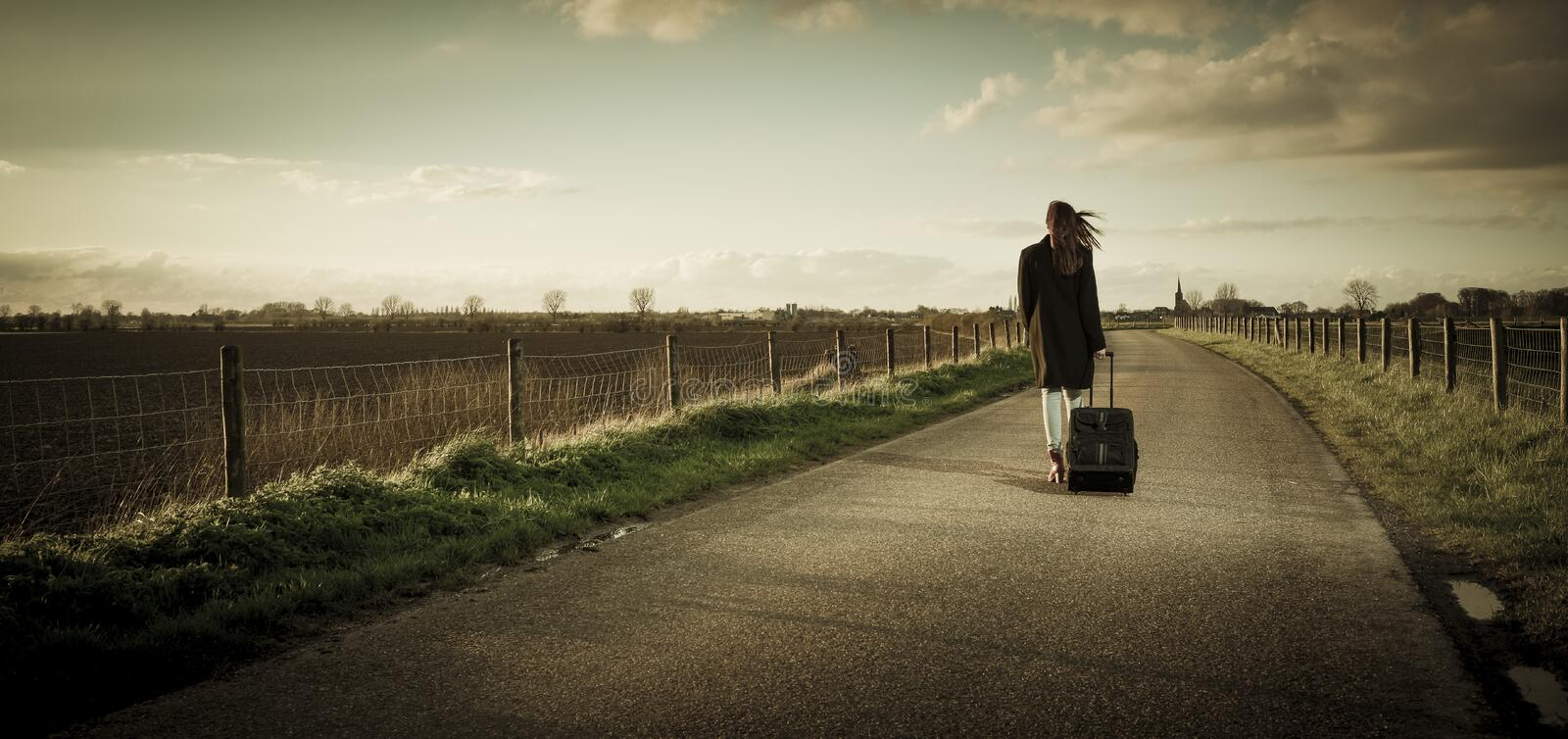 Young girl on the road. Young girl with suitcase walk on the street and leaving town royalty free stock photos
