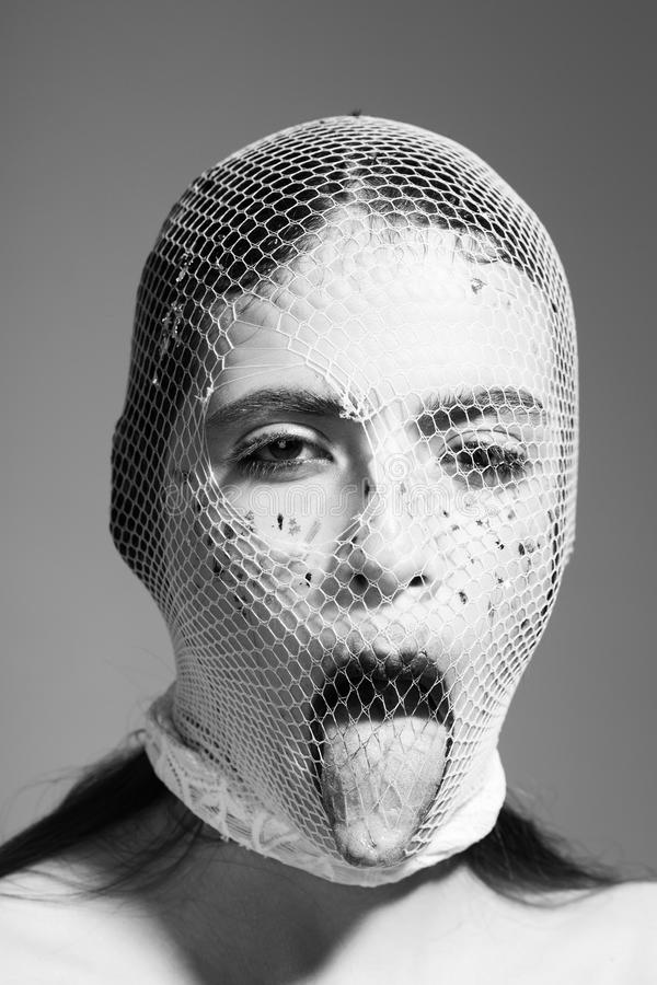 Young girl, robber bandit gangster wears mask of white fishnet. Young girl or robber bandit gangster wears mask of white fishnet stocking on face with fashion stock photo