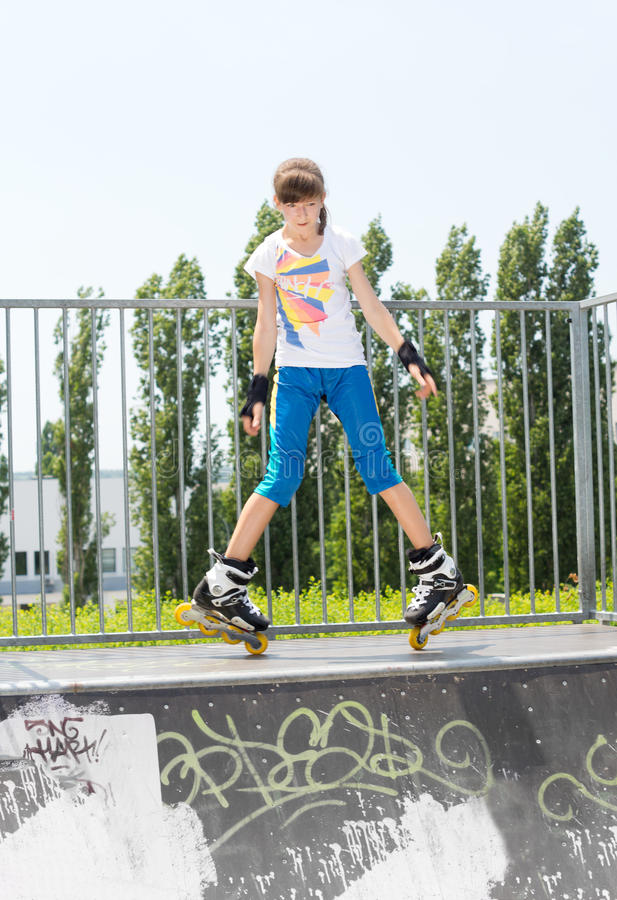 Young girl in rollerblades on a ramp