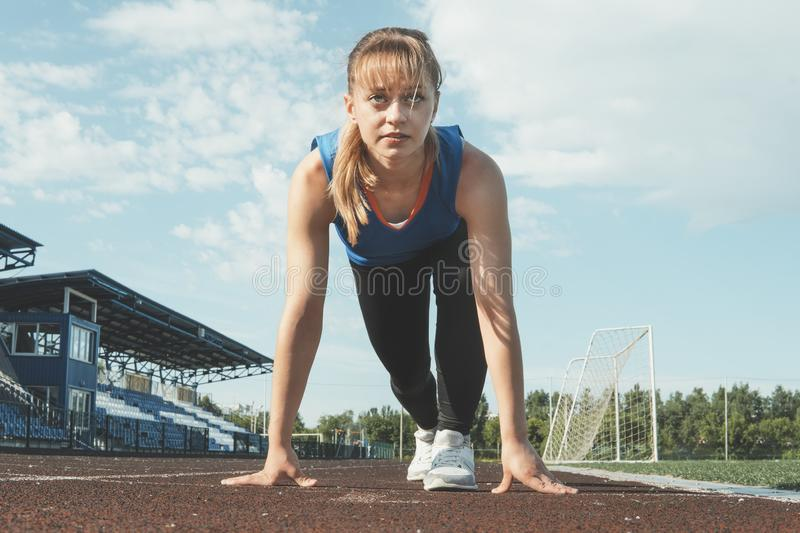 Young Girl Runner feet on track closeup focus on sport shoe. Getting ready to start.  royalty free stock photo