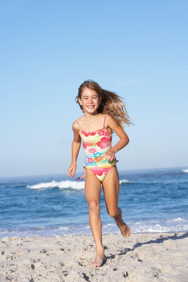 Young Girl Running Along Sandy Beach stock image
