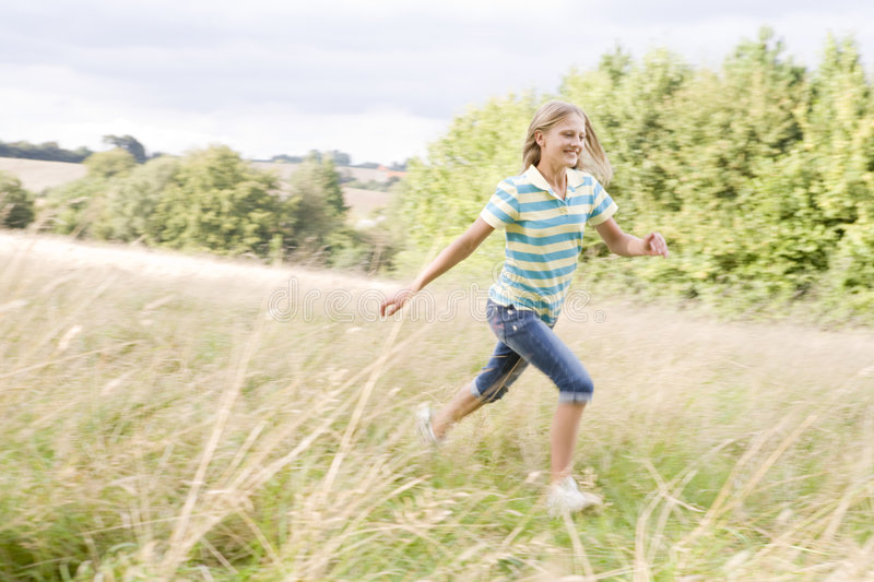 Young girl running in a field smiling royalty free stock photo