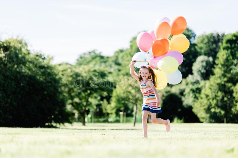 Young girl running on the grass field with balloons. stock image