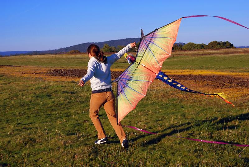 Young girl running with kite stock photo