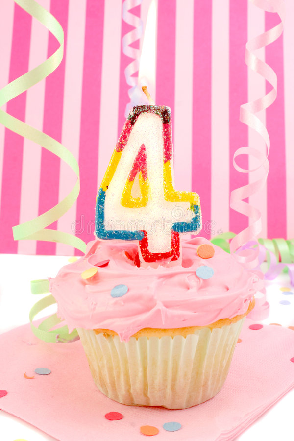 Young girl's birthday. Birthday cupcake with pink frosting and and decorative background celebrating child's fourth anniversary stock images