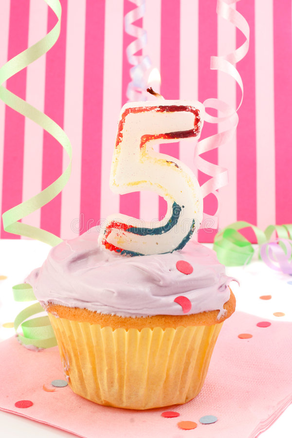 Young girl's birthday. Birthday cupcake with pink frosting and and decorative background celebrating child's fifth anniversary stock photos