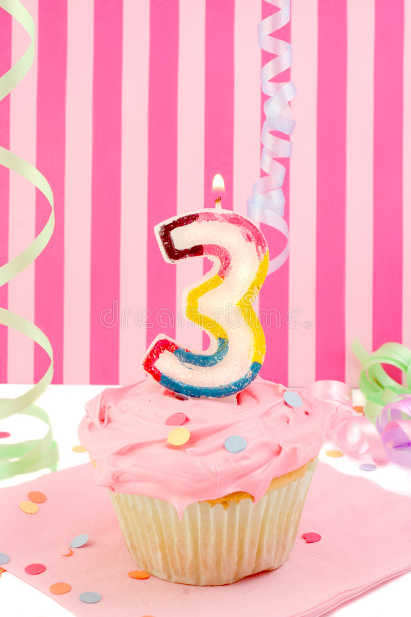 Young girl's birthday. Birthday cupcake with pink frosting and and decorative background celebrating child's third anniversary royalty free stock images