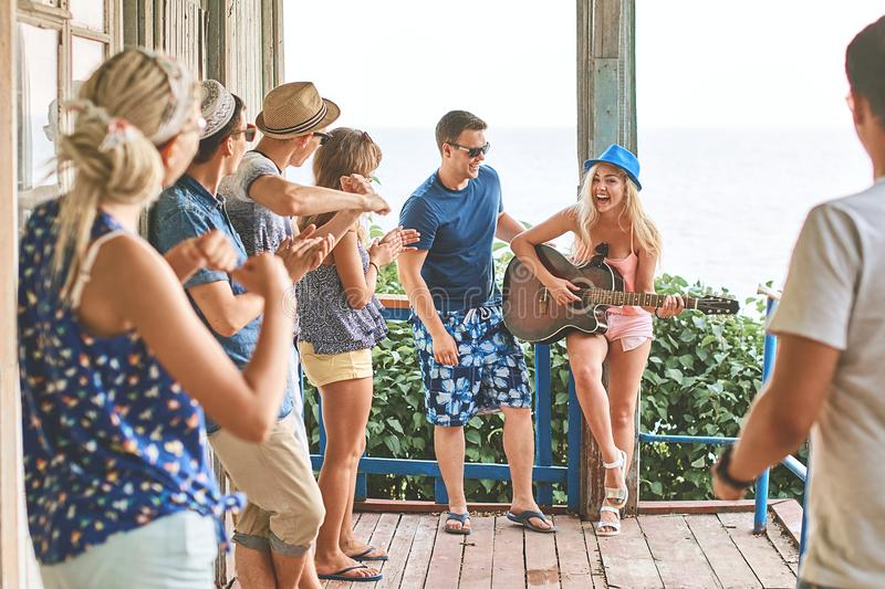 Young girl`s first attempt at playing the guitar in company of friends while hanging out on vacation at an old wooden stock images