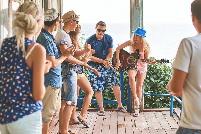 Young girl`s first attempt at playing the guitar in company of friends while hanging out on vacation at an old wooden stock photography