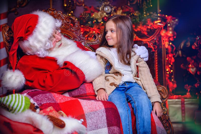 Young girl with santa. A happy young girl is sitting near Santa Claus at home. Merry Christmas and Happy New Year stock photos