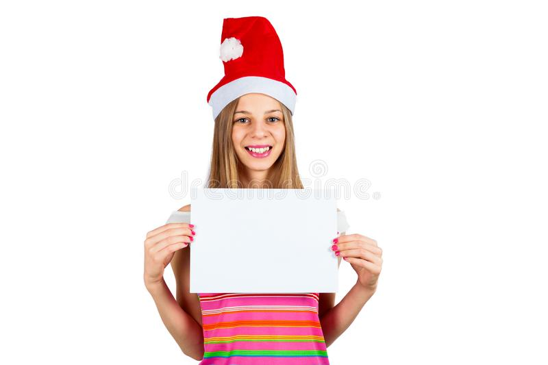 A young girl in Santa`s hat holds a white board stock image