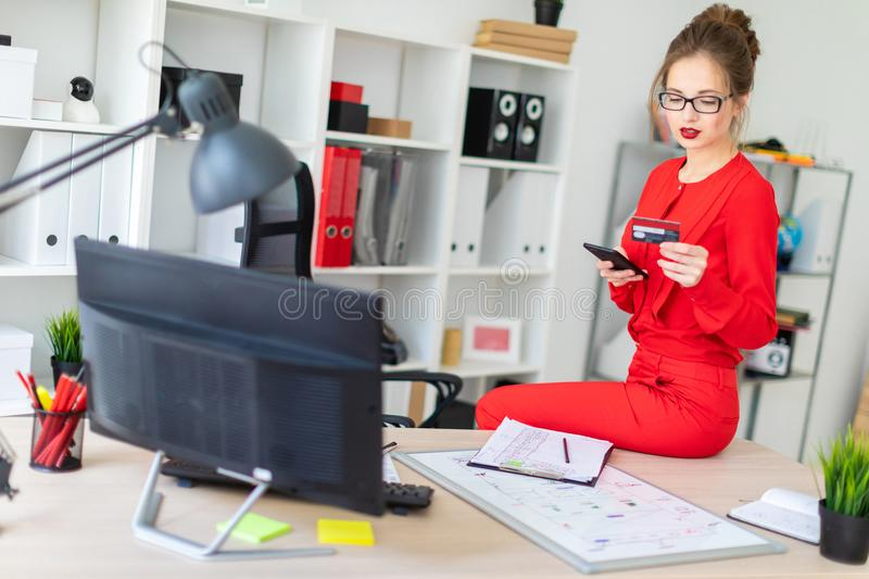 The young girl sat down on the table in her office and held a credit card and phone in her hands. Beautiful young girl in glasses and a red shirt is working in royalty free stock photo