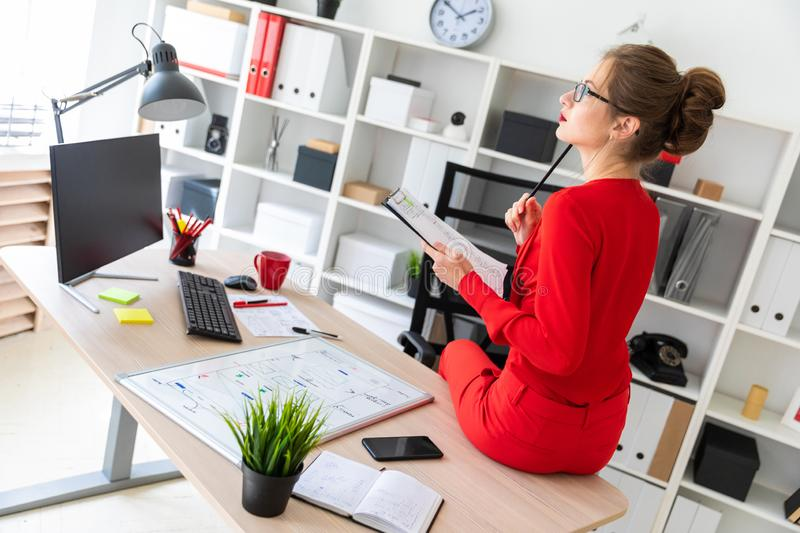 The young girl sat down on the table in her office and held a pencil and documents in her hands. Beautiful young girl in glasses and a red shirt is working in stock photography