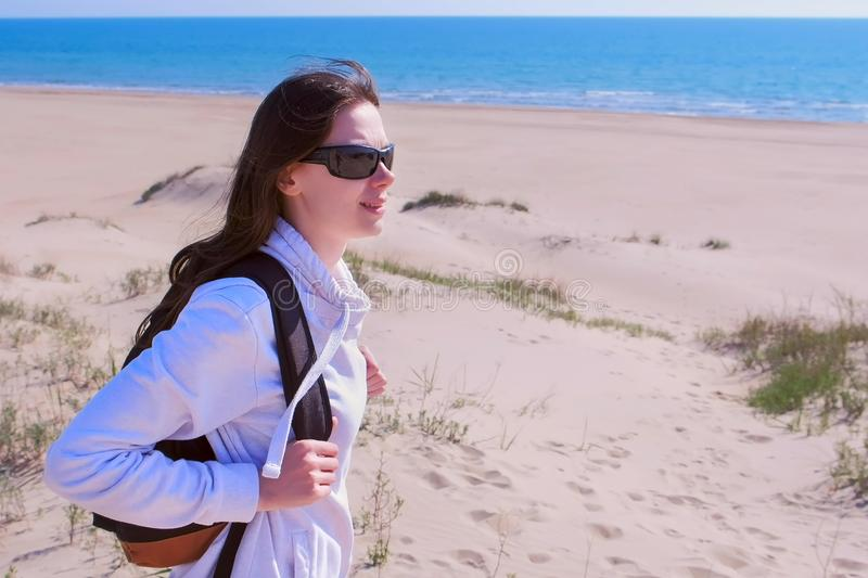Woman traveller with backpack is looking around in sea sand beach on vacation. Young girl on sea walking on empty beach off-season. Woman traveller with royalty free stock photos