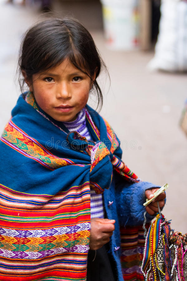 Young girl selling crafts. Pisac, Peru - May 15: Adorable native Quechua girl walking the alleyways selling hand made souvenirs in the Sacred Valley Market. May
